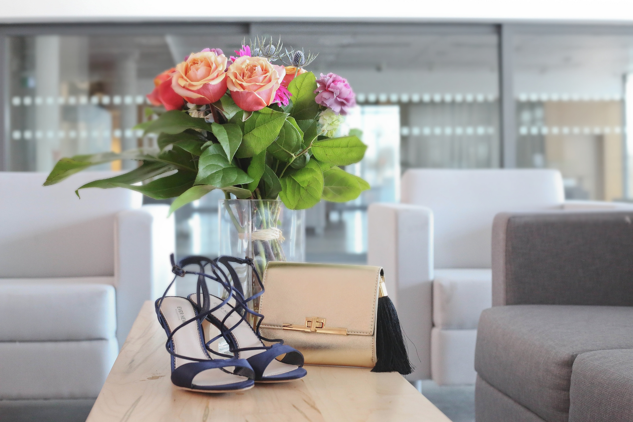 A gold clutch and navy blue heels pictured with flowers on a table