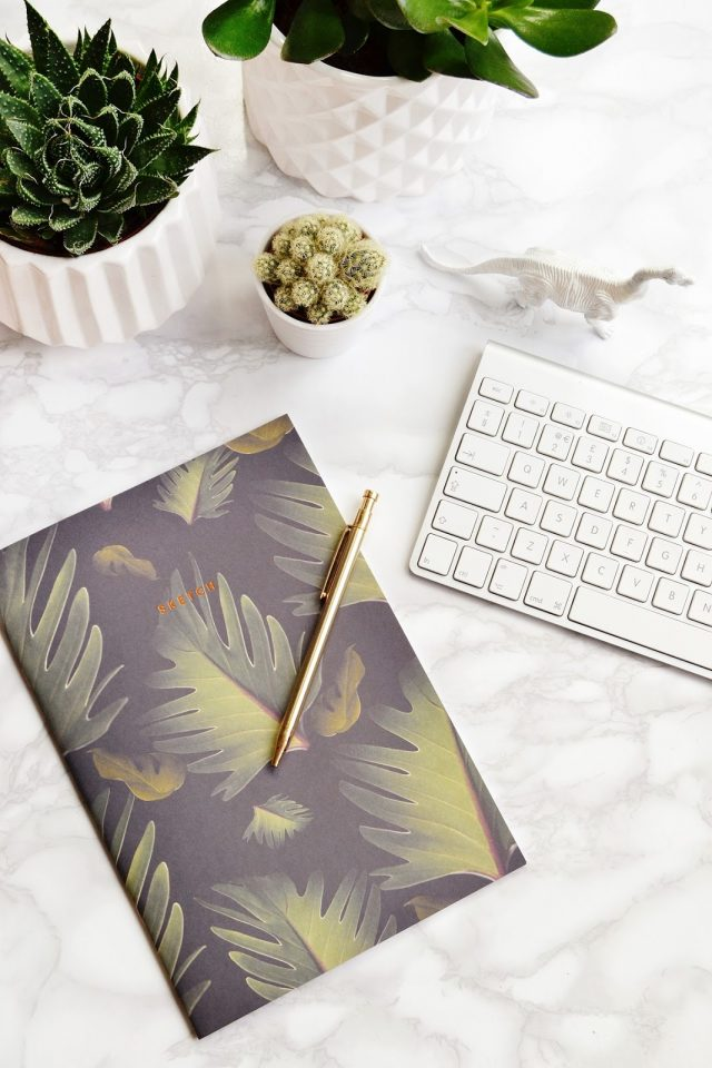 leaf notebook with a beautiful gold pen on a white desk.