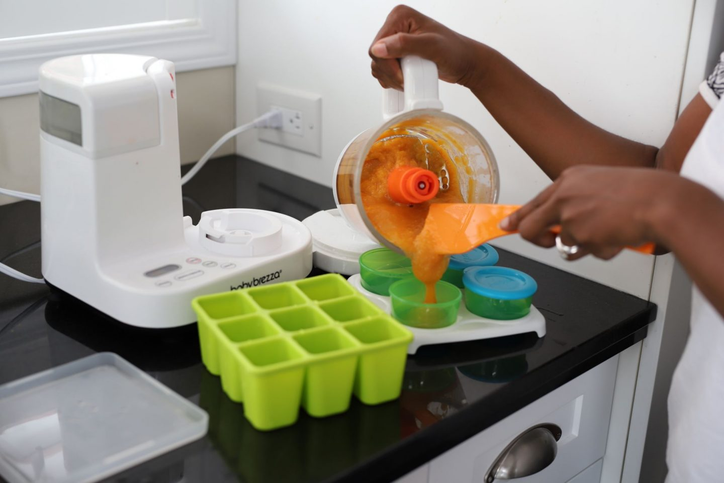 Preparing DIY baby food for storage by pouring pureed food in Nuby food storage containers