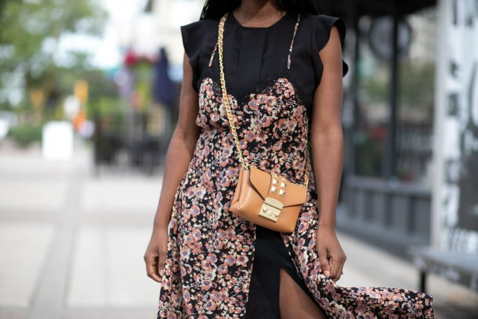 Woman wearing floral dress and camel bag
