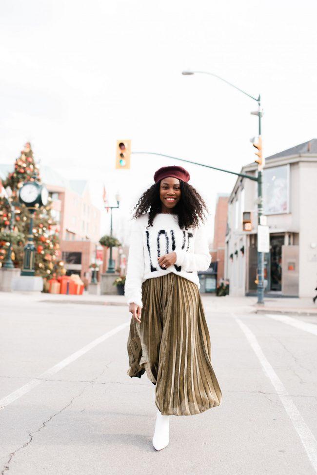Woman walking down the street wearing a  white love sweater