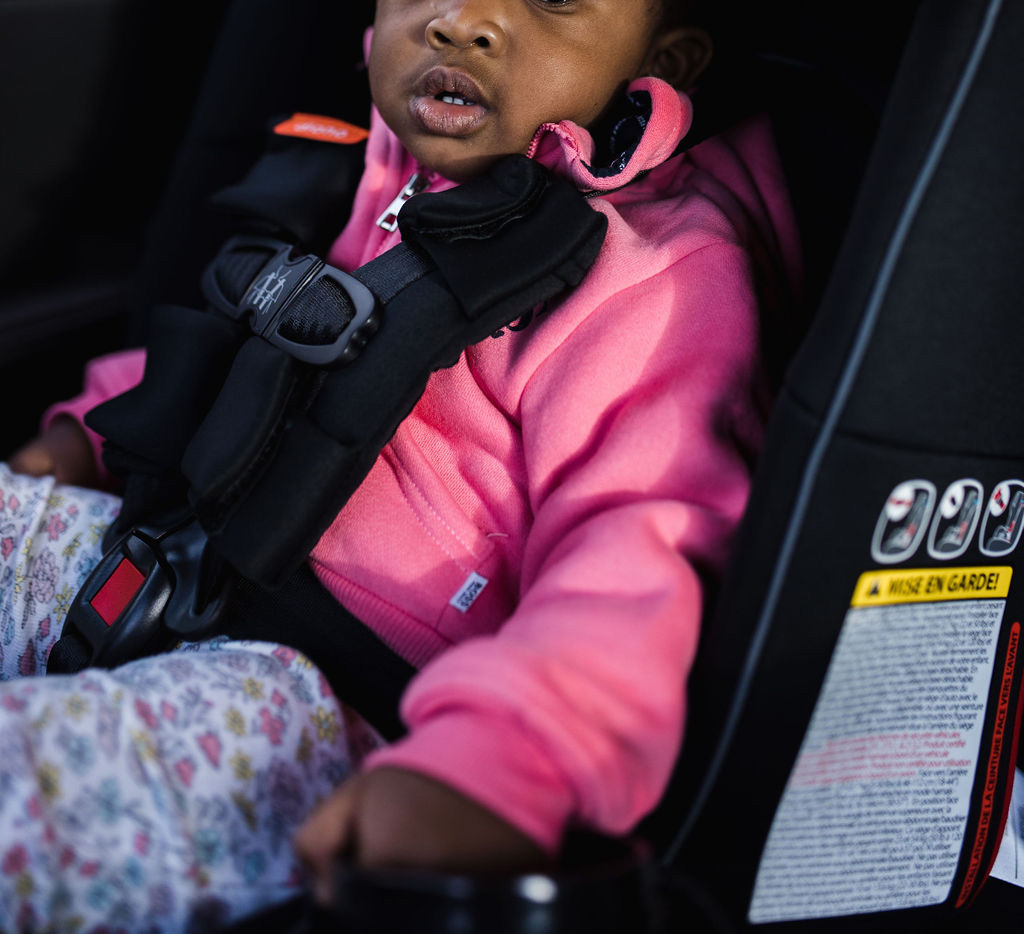 A baby girl seatig in a child car seat