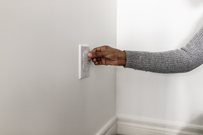 woman putting outlet covers on outlets
