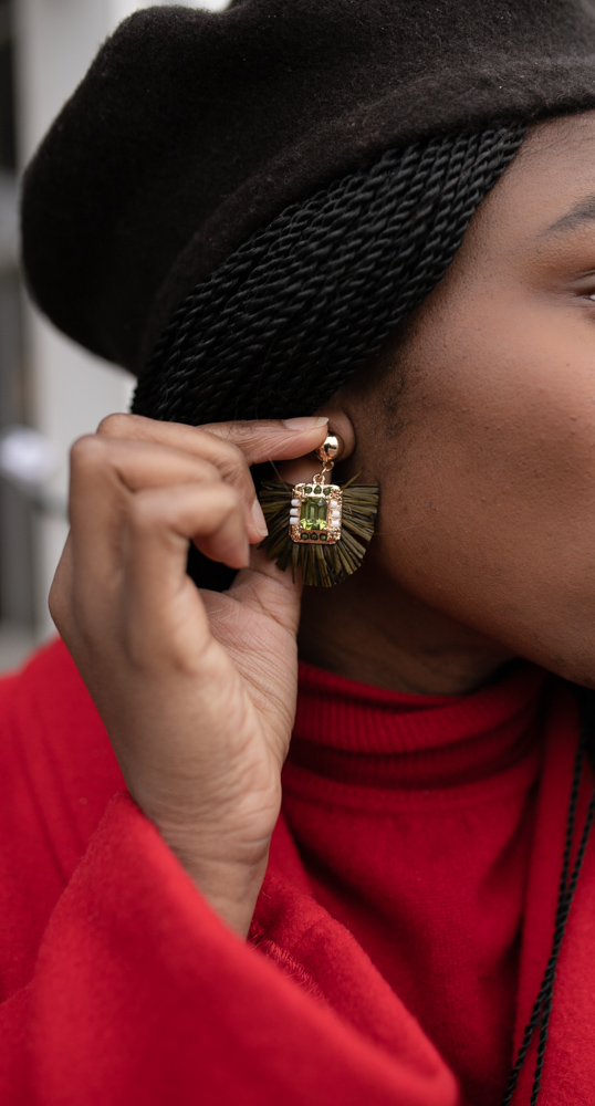 women grabbing her fringe statement earrings