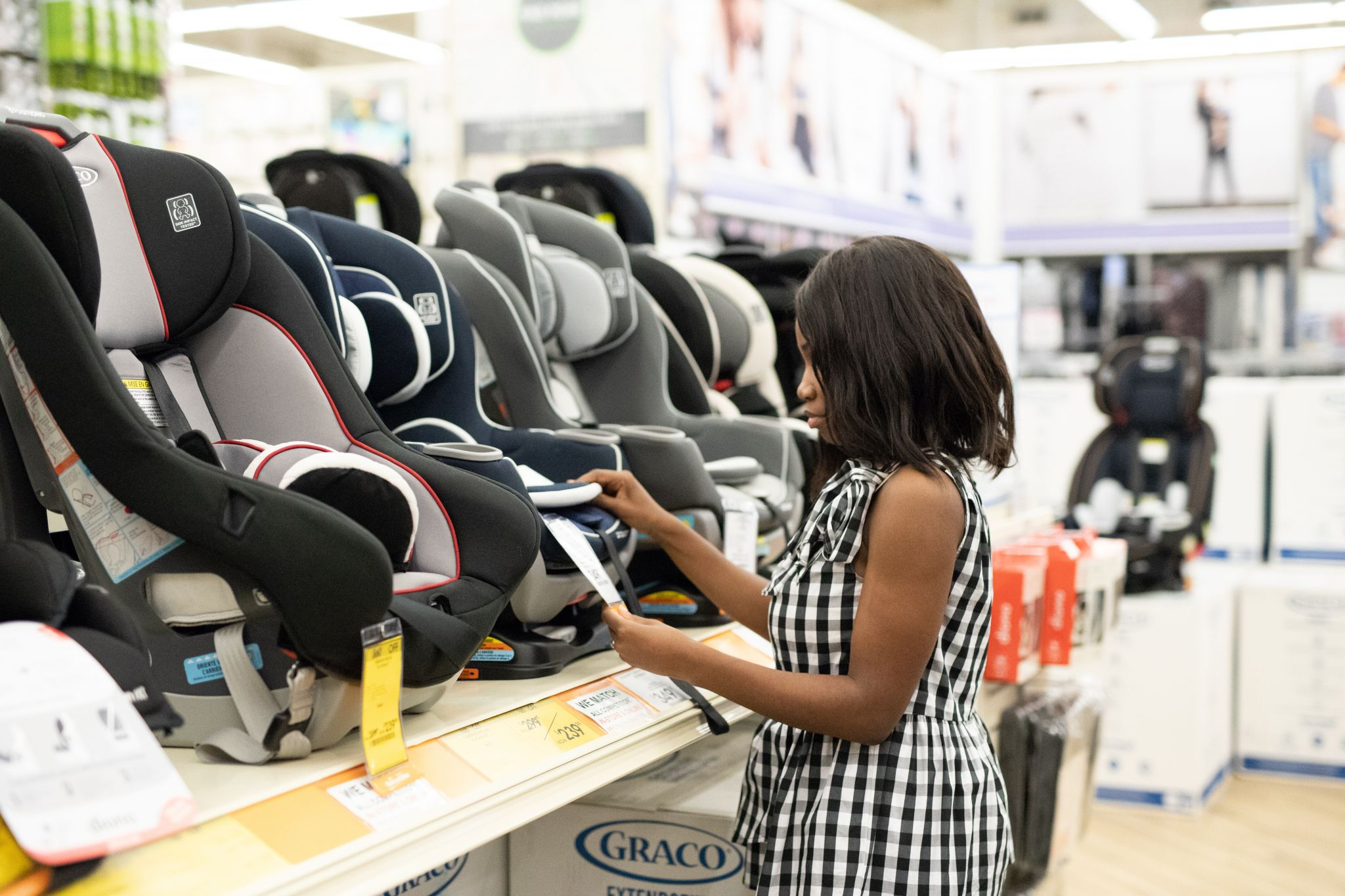 Woman shopping and looking at different child car seats