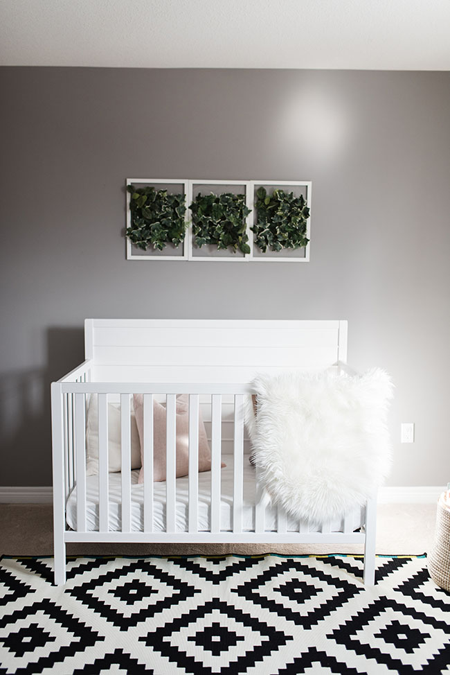 baby crib with faux greenery wall hanging as nursery wall art