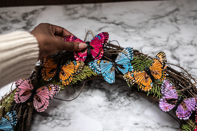 Woman gluing faux butterfly to DIY Butterfly Spring Wreath