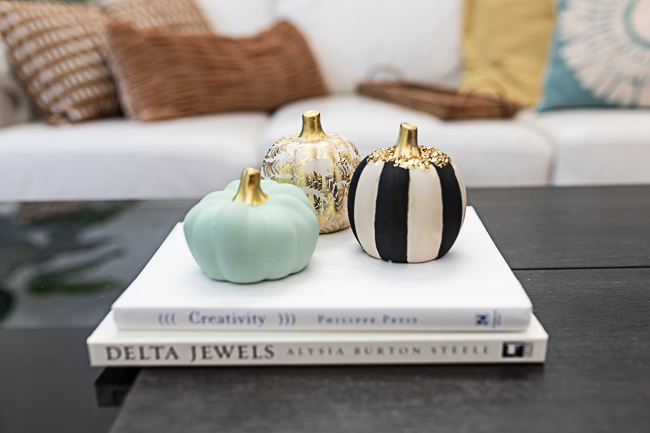A collection of decorative pumpkins on a stack of white books